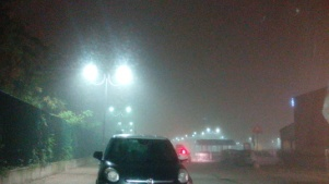 Nebbia, in un parcheggio, di sera.